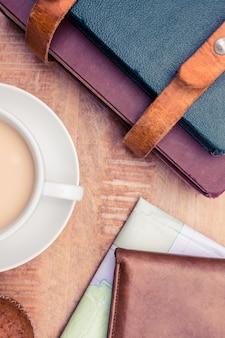 Close-up van koffie met portefeuille en agenda's op tafel