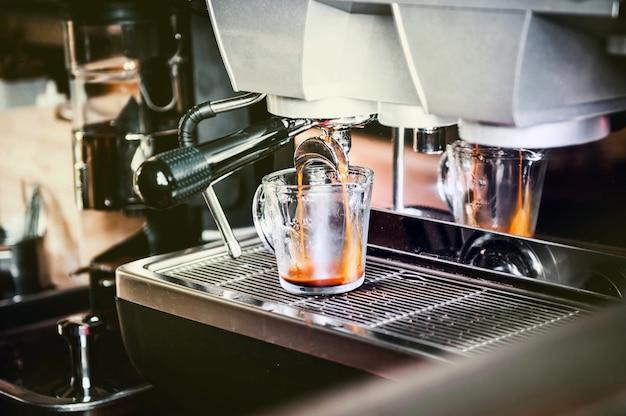 Close-up van koffiemachine die espressoproces maakt