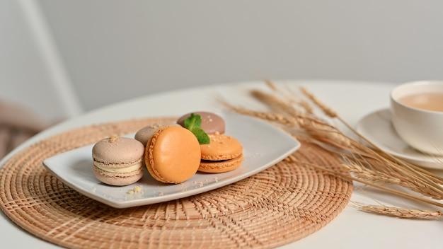Close-up van koffietafel met een plaat van franse kleurrijke macarons op placemat en kopje thee