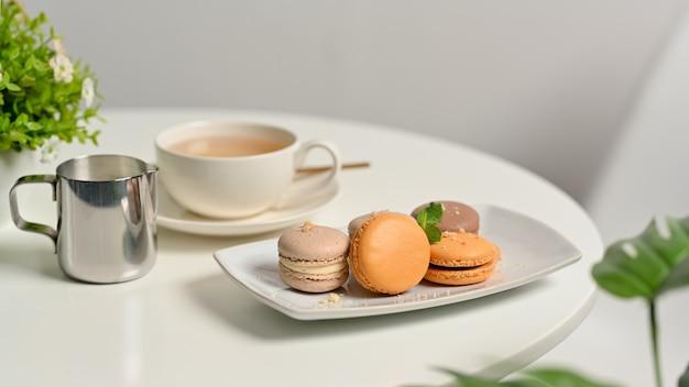 Close-up van koffietafel met franse kleurrijke macarons en kopje thee in de woonkamer