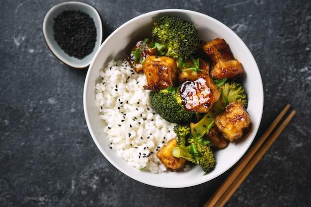 Close-up van kom met rijst, broccoli en gebakken en knapperige tofu op zwarte achtergrond