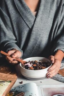 Close-up van kom met verse havermout en lepel in vrouwenhanden, gezond en voedzaam ontbijtconcept.