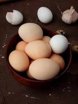 Close-up van kom vol eieren met knoflook op kastanjebruine bakground