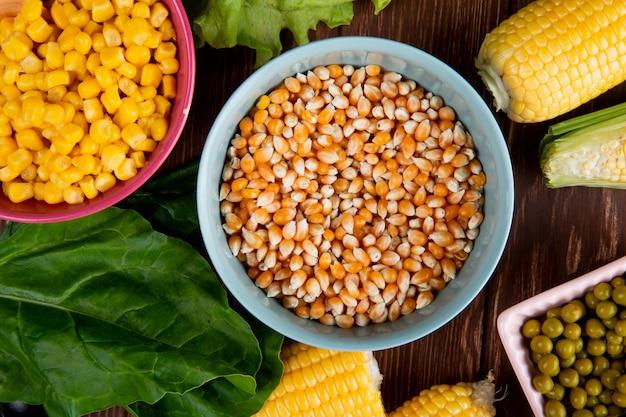 Close-up van kom vol maïs zaden met spinazie gekookte maïs zaden groene erwten op houten tafel