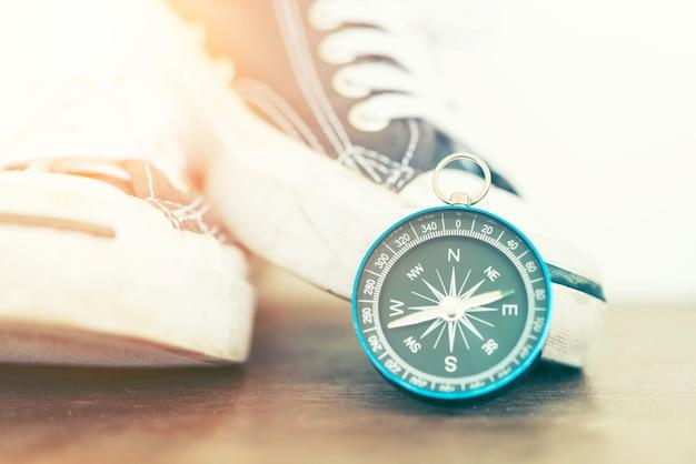Close-up van kompas en sneakers op hout met zonsonderganglicht.