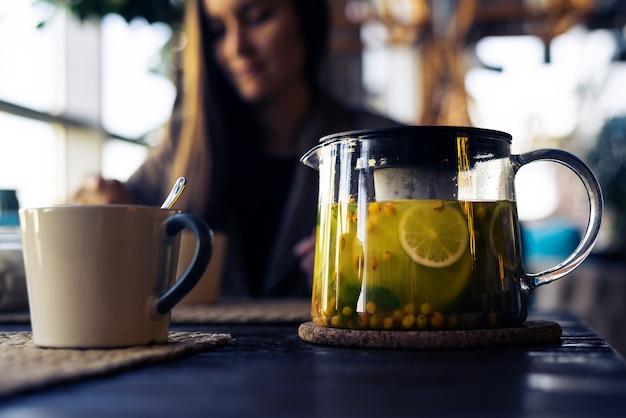 Close-up van kop en glastheepot met duindoornthee met citroen en kruiden, vrouw met smartphone op vaag