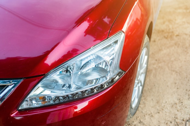 Close-up van koplamp van rode auto in openlucht.