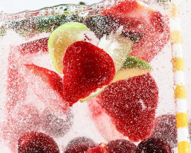 Close-up van koude en verse limonade met aardbei-kersenmuntblaadjes en ijsblokjes