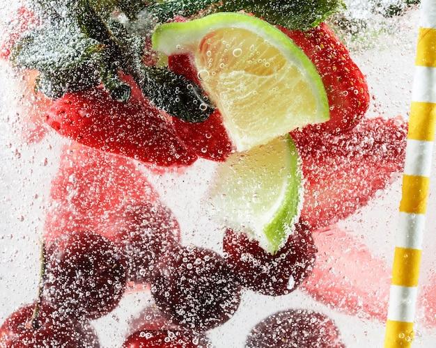 Close-up van koude en verse limonade met aardbeien, kersen, muntblaadjes en ijsblokjes. textuur van verkoelende zomerdrank met macrobellen op glas. bruisend of drijvend naar de bovenkant van het oppervlak.