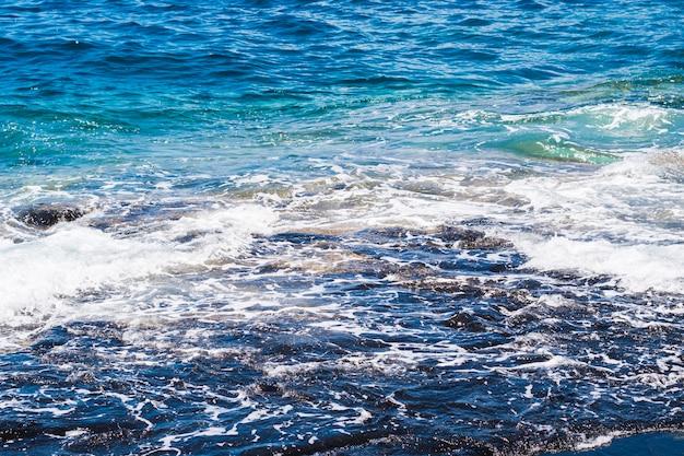 Close-up van kristallijn golvend water op het strand