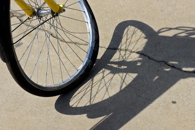 Close-up van krom fietswiel, projecterende surrealistische schaduw op stoep