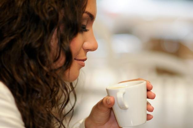 Close-up van krullend haar vrouw het drinken van een kopje koffie
