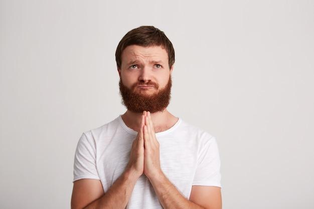 Close-up van lachende aantrekkelijke jonge man hipster met baard draagt t-shirt en bidt