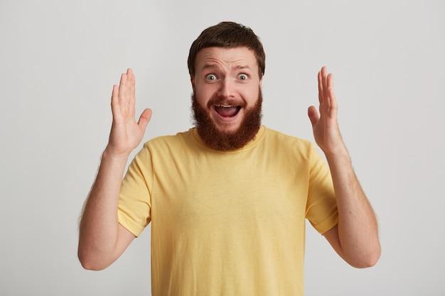Close-up van lachende aantrekkelijke jonge man hipster met baard draagt t-shirt voelt zich verrast