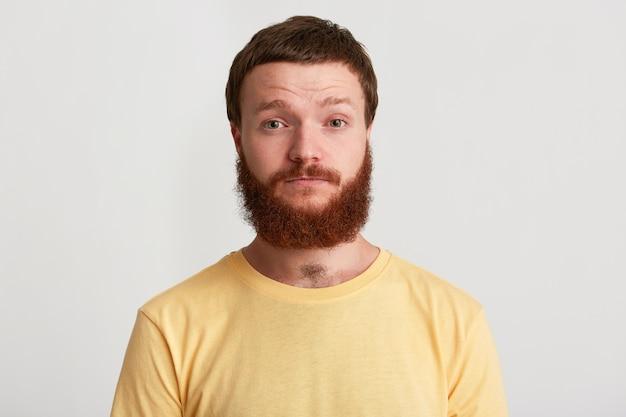 Close-up van lachende aantrekkelijke jonge man hipster met baard draagt t-shirt