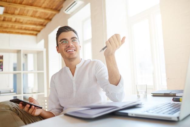 Close-up van lachende aantrekkelijke jonge zakenman draagt een wit overhemd op kantoor