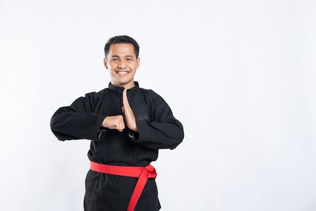 Close-up van lachende aziatische man met pencak silat uniform staande met respectvolle handgebaren