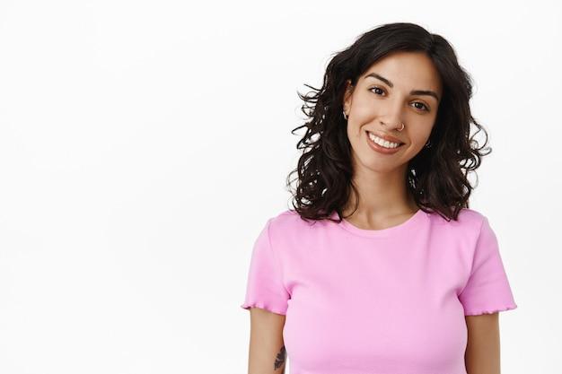 Close-up van lachende brunette israëlische vrouw, doorboorde neus en gelukkige glimlach, zelfverzekerd en gezond, gevaccineerd, campagne voor covid-19-vaccinatie op wit