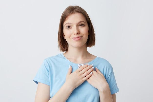 Close-up van lachende charmante jonge vrouw draagt blauwe t-shirt houdt handen op haar hart-gebied