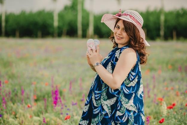 Close-up van lachende jonge vrouw en toekomstige moeder die haar babyschoenen vasthoudt en naar de camera kijkt in een veld vol bloemen