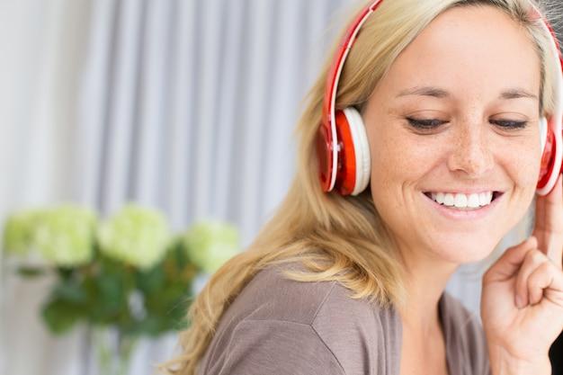 Close-up van lachende jonge vrouw in koptelefoon