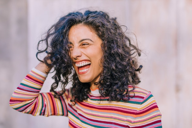 Close-up van lachende jonge vrouw met de hand op het hoofd