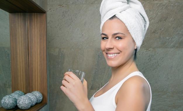 Close-up van lachende jonge vrouw met een handdoek over haar met een glas schoon water in de badkamer. gezondheid en schoonheidsconcept.
