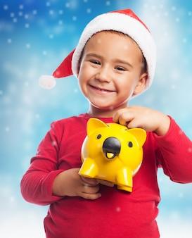 Close-up van lachende jongen met zijn gele piggybank