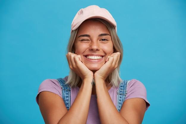 Close-up van lachende mooie blonde jonge vrouw draagt roze pet en violet t-shirt ziet er gelukkig uit en knipoogt geïsoleerd over blauwe muur