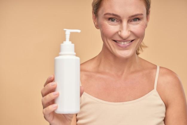 Close up van lachende mooie vrouw met vochtinbrengende lichaamscrème