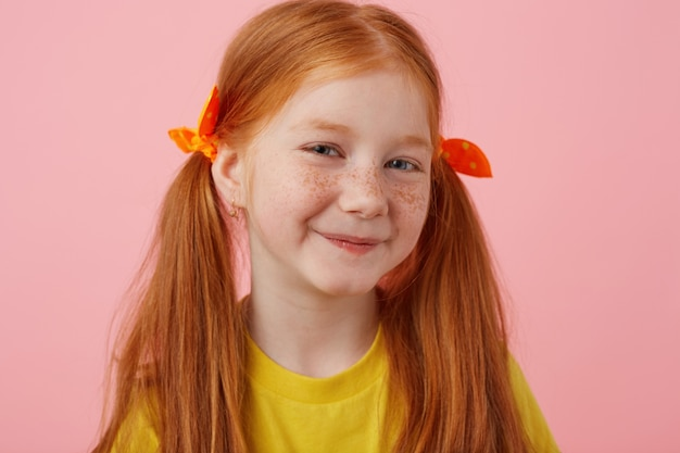 Close-up van lachende petite sproeten roodharige meisje met twee staarten, glimlachend en ziet er schattig uit, draagt in geel t-shirt, staat op roze achtergrond.
