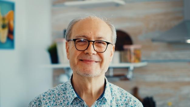 Close up van lachende senior man in keuken kijken camera dragen van een bril. portret van een ontspannen oudere oudere persoon in de ochtend, genietend van een vers warm drankje. gezond lachend volwassen gezicht