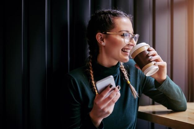 Close-up van lachende tienermeisje zit in cafetaria naast raam, koffie drinken en slimme telefoon te houden terwijl u via raam kijkt.