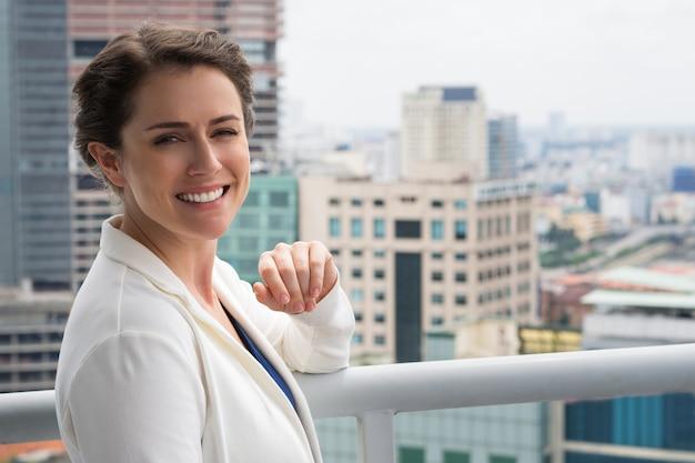 Close-up van lachende volwassen zakenvrouw op balkon