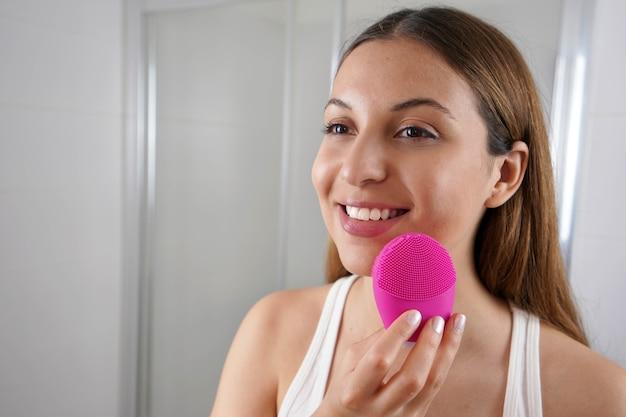 Close up van lachende vrouw huid reinigen met ultrasone siliconen borstel in de badkamer