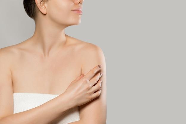 Close up van lachende vrouw zachte huid op schouder aanraken over grijze achtergrond. schoonheidsprocedure, advertentieconcept voor lichaamscrème. cosmetische vochtinbrengende lotion