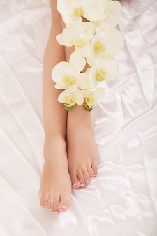 Close-up van lange vrouwelijke benen met een perfect gladde, zachte huid en bloemen