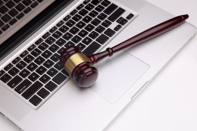 Close-up van laptop en hamer op tafel in de rechtszaal.