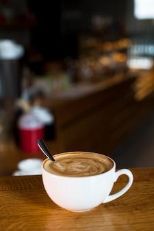 Close-up van latte koffiekopje boven tafel