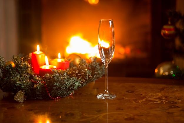 Close-up van lege champagnefluit op kersttafel voor brandende open haard