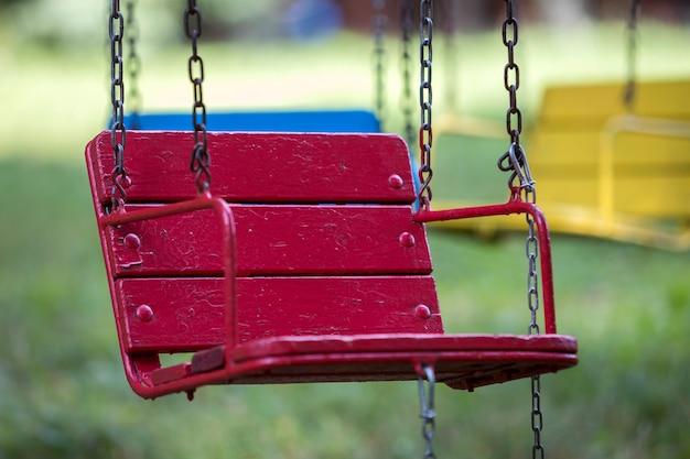 Close-up van lege houten blauwe, gele, uitstekende zetels van het multi-gekleurde carrousel hangen op kettingen.