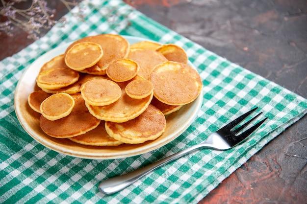 Close-up van lekkere pannenkoeken en vork op handdoek