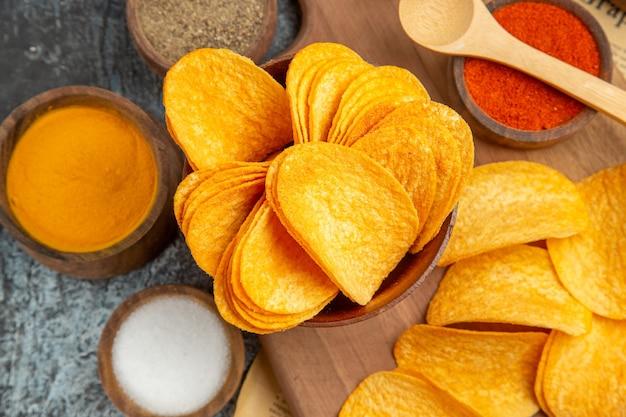 Close-up van lekkere zelfgemaakte chips gesneden aardappelschijfjes op houten snijplank en verschillende kruiden op krant op grijze tafel