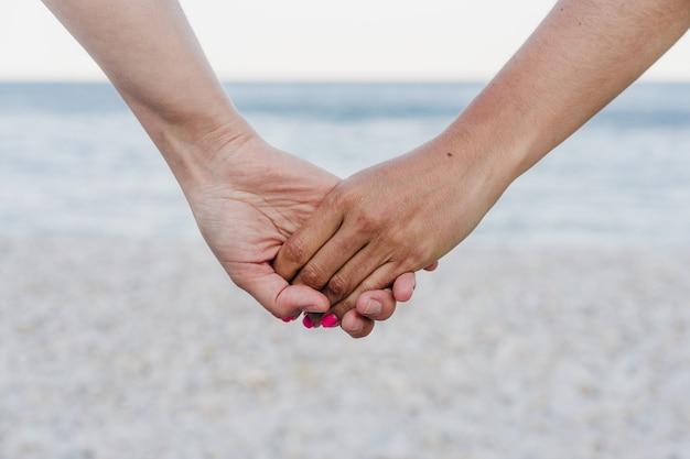 Close-up van lesbisch koppel hand in hand op het strand tijdens zonsondergang. liefde is liefde en lgtbi-concept