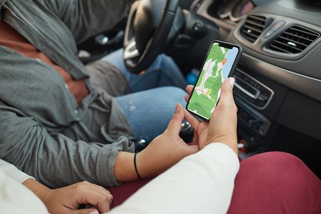Close-up van lesbisch koppel met behulp van navigator op mobiele telefoon tijdens het reizen met de auto