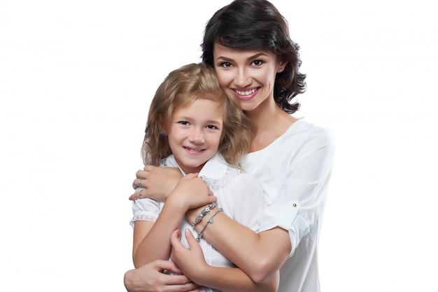 Close-up van leuke familie paar: mooie moeder en haar kleine dochtertje. ze zijn erg blij met een mooie glimlach. ze dragen witte t-shirts. foto is gemaakt