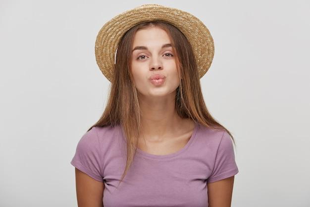 Close up van leuke mooie vrouw in casual outfit in een strooien hoed met een roze lint waait kus verzenden