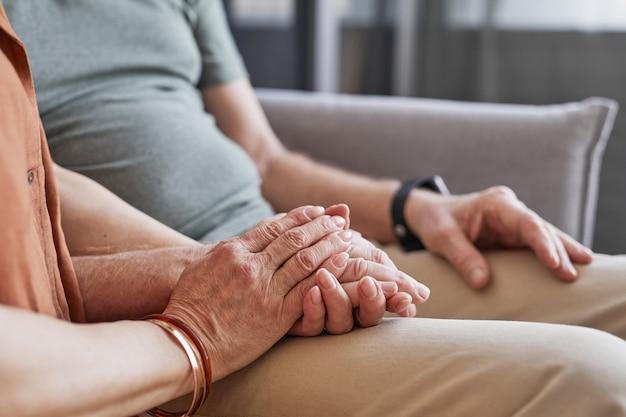 Close-up van liefdevol senior koppel hand in hand terwijl ze samen op de bank zitten, kopieer ruimte