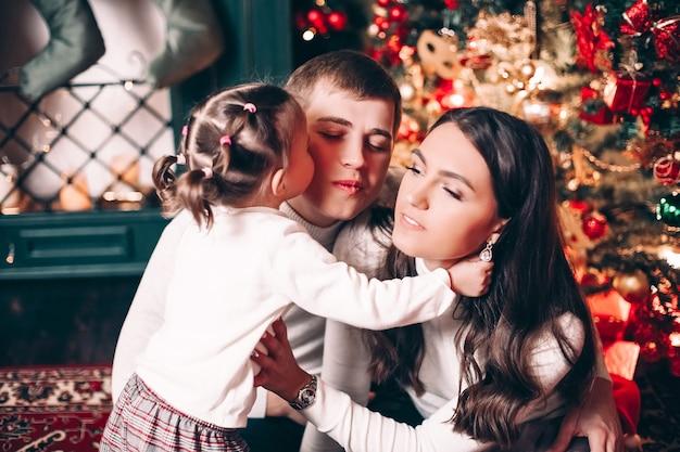 Close-up van liefdevolle meisje kuste haar moeder met tederheid zittend door de boom
