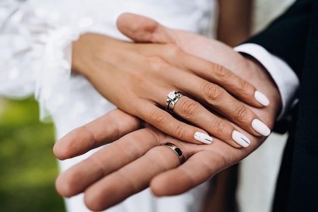 Close-up van liefdevolle paar hand in hand. liefde, valentijn en bruiloft concept. net getrouwd stel met ringen en liefde. bovenaanzicht. reclame voor juweliersalon. bruiloft banner. kapperszaak.
